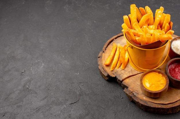 Vooraanzicht lekkere frietjes met sauzen op donkere ruimte