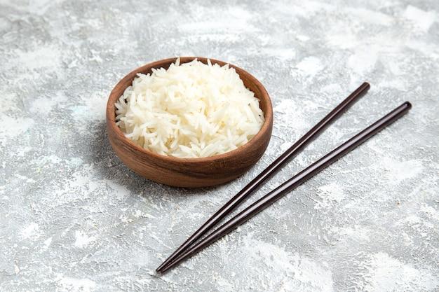 Vooraanzicht lekkere gekookte rijst in bruine plaat op witte ruimte