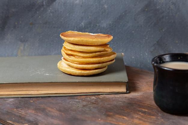 Vooraanzicht lekkere heerlijke pannenkoeken met zwarte kop melk op het grijze ontbijt van de achtergrondvoedselmaaltijd