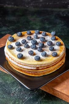 Vooraanzicht lekkere honingcake met bosbessen in plaat donker oppervlak