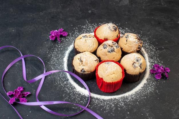 Vooraanzicht lekkere kleine cakes met chocolade op donkere tafel