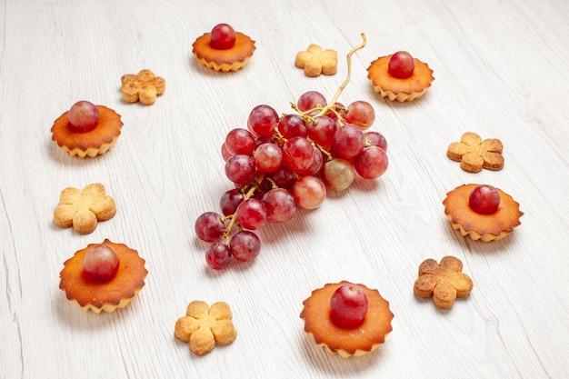 Vooraanzicht lekkere kleine taarten met druiven en koekjes op witte achtergrond fruit thee dessert cookie biscuit cake pie