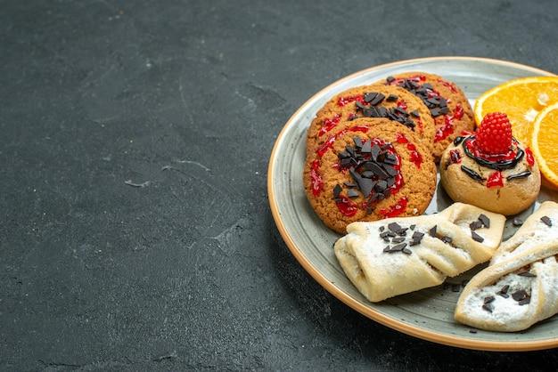 Vooraanzicht lekkere koekjes met fruitige gebakjes en stukjes sinaasappel op donkere oppervlaktevruchten, zoete caketaart theesuiker