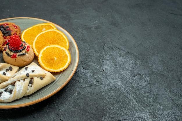 Vooraanzicht lekkere koekjes met fruitige gebakjes en stukjes sinaasappel op het donkere oppervlak fruit zoete cake taart thee suiker