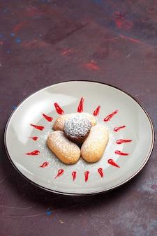 Vooraanzicht lekkere koekjes met suikerpoeder en rood glazuur in plaat op donkere ruimte