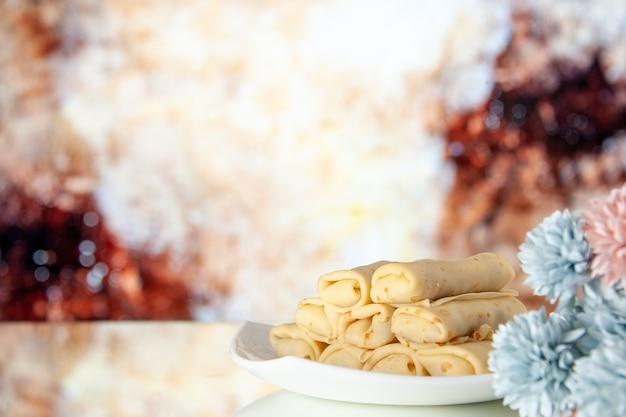 Vooraanzicht lekkere opgerolde pannenkoeken op lichte achtergrond melk ontbijt cake suiker zoete ochtend bloem kleur