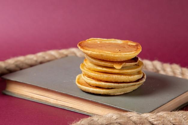 Vooraanzicht lekkere pannekoeken die op het voorbeeldenboek op het roze voedsel van het achtergrond zoete suikerontbijt worden gebakken