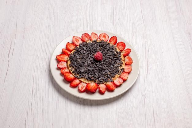 Vooraanzicht lekkere pannenkoeken met aardbeien en chocoladeschilfers op een wit bureau, zoete bakcake, biscuitbessenfruit