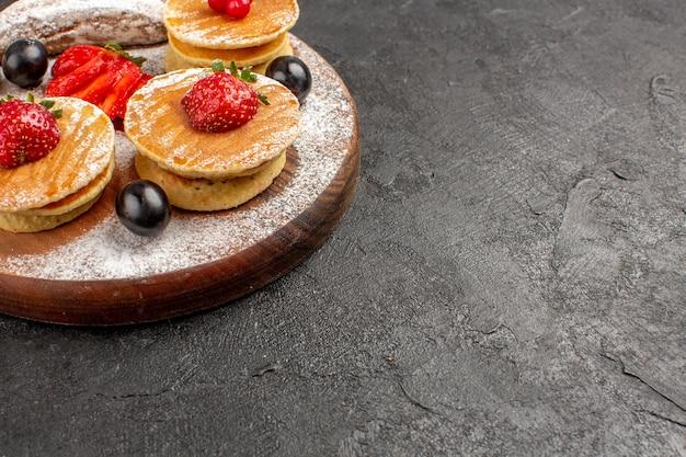 Vooraanzicht lekkere pannenkoeken met fruit en cakes op de donkere zoete cake van het oppervlaktefruit