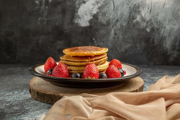 Vooraanzicht lekkere pannenkoeken met fruit en honing op lichte oppervlakte zoete fruitmelk