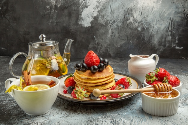 Vooraanzicht lekkere pannenkoeken met fruit en thee op licht oppervlak zoet fruit ontbijt