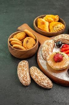 Vooraanzicht lekkere pannenkoeken met fruit en zoete cakes op het donkere dessert van de oppervlakte zoete cake