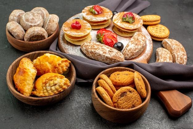 Vooraanzicht lekkere pannenkoeken met fruit en zoete taarten op de donkere zoete cake van het oppervlaktedessert