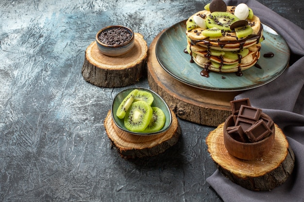 Vooraanzicht lekkere pannenkoeken met gesneden fruit en chocolade op donkergrijs oppervlak zoet ontbijt suiker fruit cake dessert