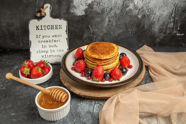 Vooraanzicht lekkere pannenkoeken met honing en fruit op het lichte oppervlak zoete melkfruit