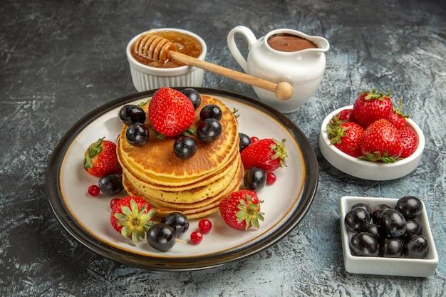 Vooraanzicht lekkere pannenkoeken met honing en fruit op lichte cake van het oppervlakte zoete fruit
