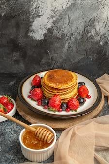 Vooraanzicht lekkere pannenkoeken met honing en fruit op lichte vloer zoete melkfruit