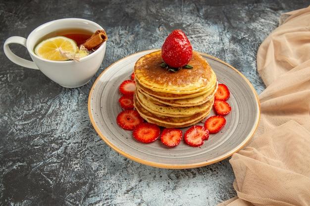 Vooraanzicht lekkere pannenkoeken met kopje thee en fruit op licht oppervlak cake zoet fruit