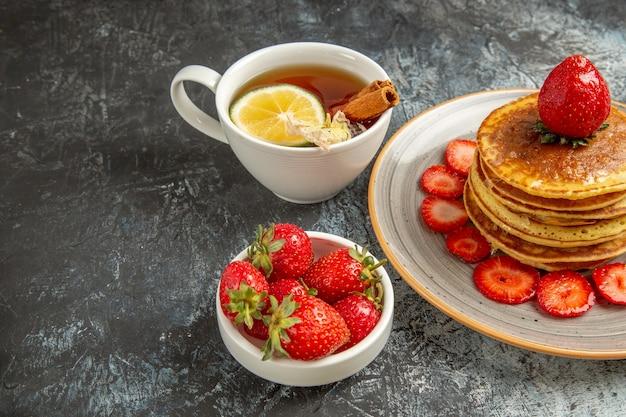 Vooraanzicht lekkere pannenkoeken met thee en fruit op de lichte zoete cake van het oppervlaktefruit