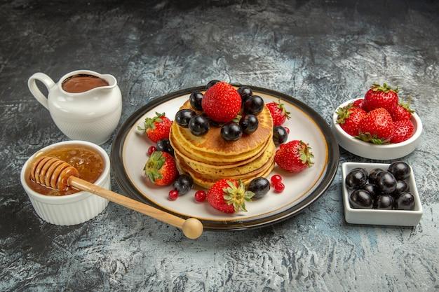 Vooraanzicht lekkere pannenkoeken met vers fruit en honing op lichte oppervlak fruit zoete cake