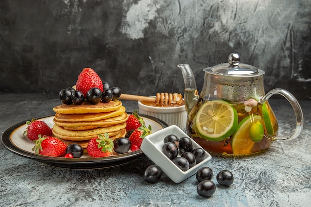 Vooraanzicht lekkere pannenkoeken met vers fruit op de lichte zoete cake van het oppervlaktefruit