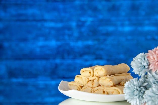 Vooraanzicht lekkere pannenkoeken op de blauwe achtergrond cake suiker dessert kleur maaltijd koekje ontbijt ochtend zoet