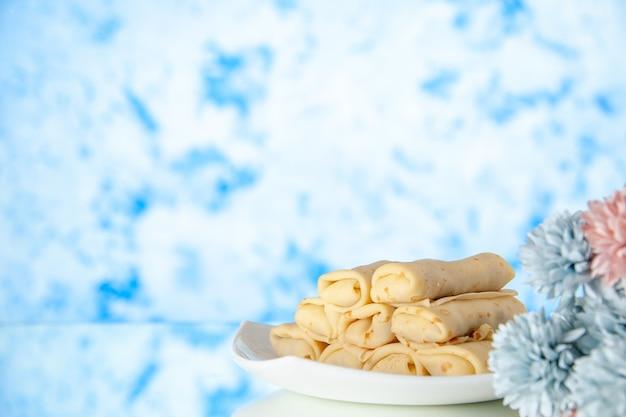 Vooraanzicht lekkere pannenkoeken op lichtblauwe achtergrond cake suiker dessert maaltijd koekje ontbijt ochtend kleur zoet
