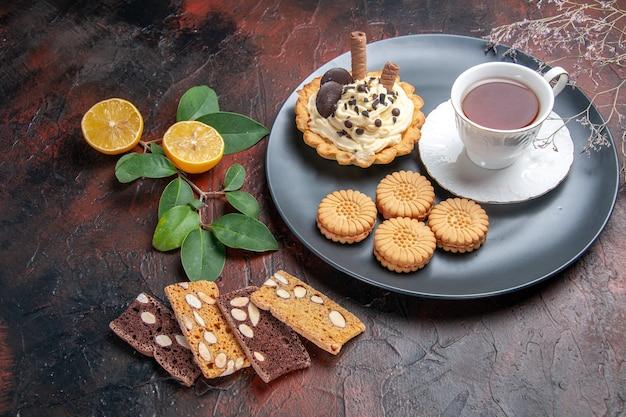 Vooraanzicht lekkere romige cake met thee op het donkere dessert van de lijst zoete cake