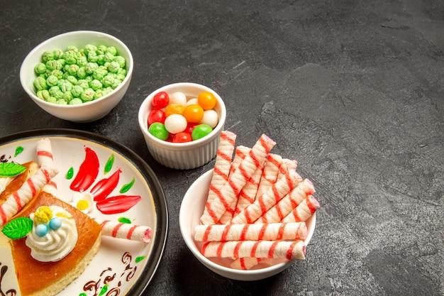Vooraanzicht lekkere slagroomtaart in ontworpen bord met snoepjes op donkere ruimte