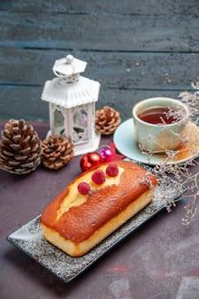 Vooraanzicht lekkere taart lang gevormd op de donkere achtergrond cake biscuit suiker koekjes taart zoete thee