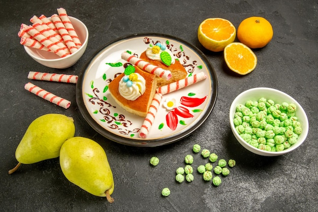 Vooraanzicht lekkere taartschijfjes met fruit en snoep op grijze ruimte
