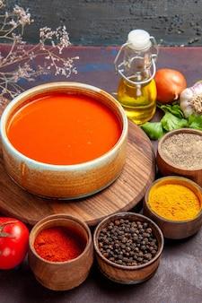 Vooraanzicht lekkere tomatensoep met kruiden op een donkere ruimte
