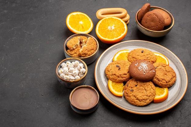 Vooraanzicht lekkere zandkoekjes met gesneden sinaasappels op een donkere achtergrond, fruit, citruskoekje, zoete cakekoekje