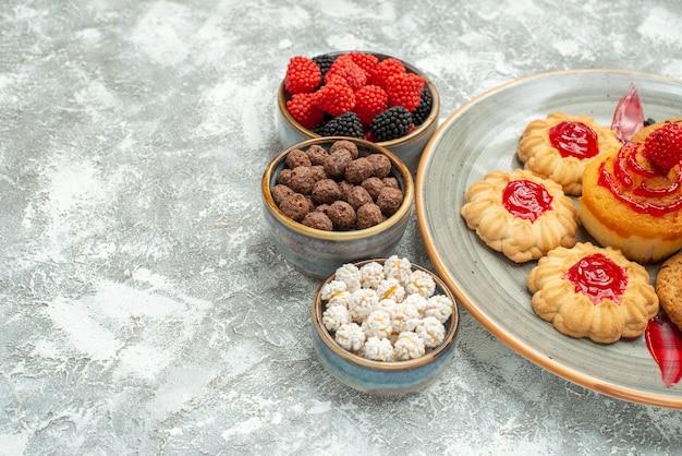 Vooraanzicht lekkere zandkoekjes met koekjes en snoepjes op een witte ruimte