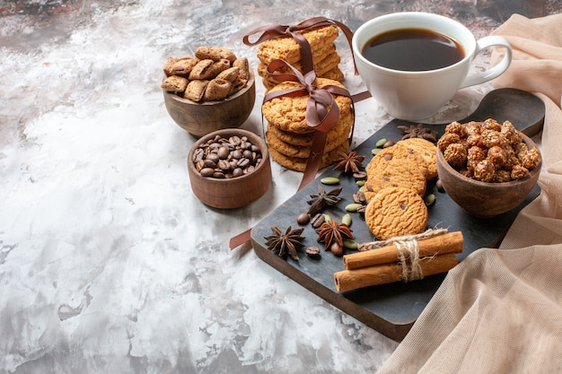 Vooraanzicht lekkere zoete koekjes met koffiezaden en kopje koffie op lichte achtergrondkleur cacaosuiker theekoekje zoete caketaart