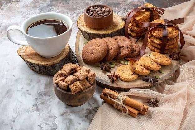 Vooraanzicht lekkere zoete koekjes met kopje koffie op de lichte achtergrondkleur cacao suiker thee cake cookie zoete taart