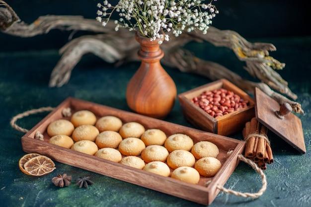 Vooraanzicht lekkere zoete koekjes met pinda's op donkere ondergrond