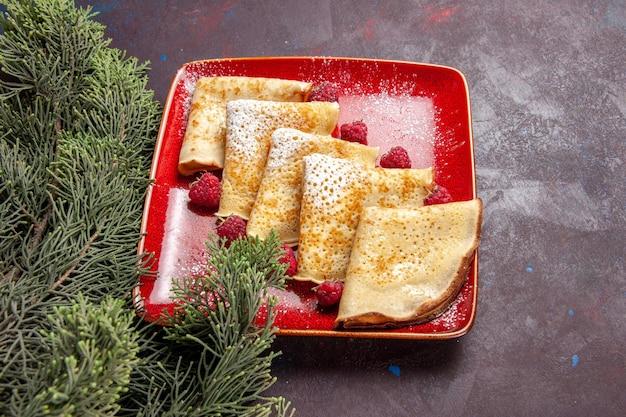 Vooraanzicht lekkere zoete pannenkoeken met frambozen op donkere ruimte