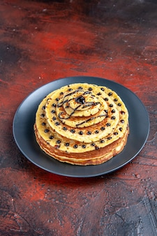 Vooraanzicht lekkere zoete pannenkoeken met suikerglazuur op donkere achtergrond