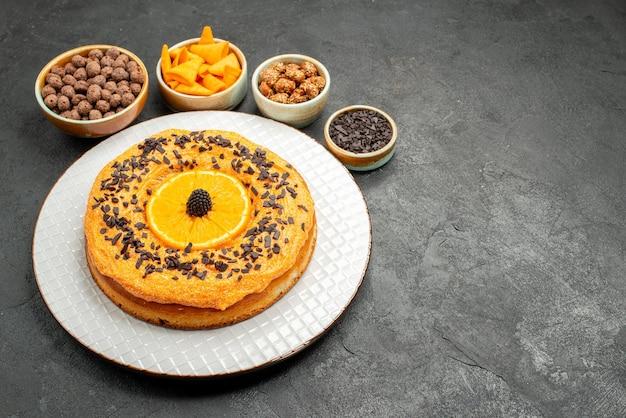 Vooraanzicht lekkere zoete taart met sinaasappelschijfjes op donkergrijze taartkoekjesdessert zoete taartthee als achtergrond