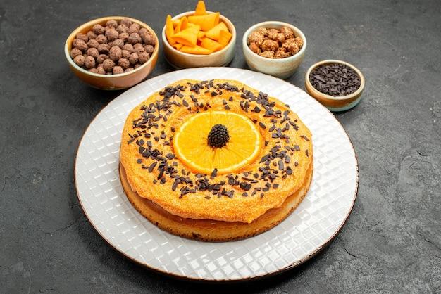 Vooraanzicht lekkere zoete taart met stukjes sinaasappel op grijze achtergrond taart biscuit dessert zoete cake thee