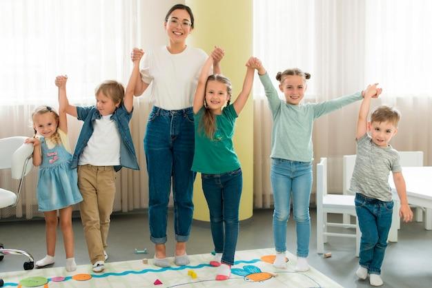 Vooraanzicht leraar en kinderen samen poseren