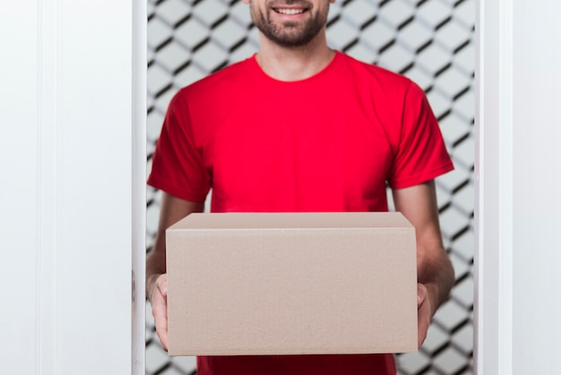 Vooraanzicht levering man draagt rode uniforme close-up op doos