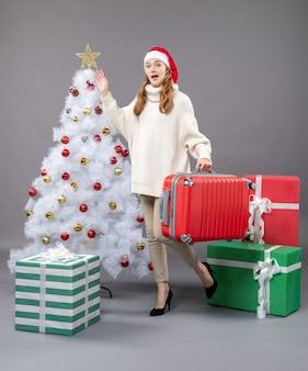 Vooraanzicht lopende vrouw die met santahoed haar reistas houdt en de ster van de kerstmisboom toont