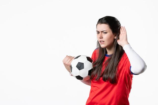 Vooraanzicht luisteren jonge vrouw in sportkleren met voetbal