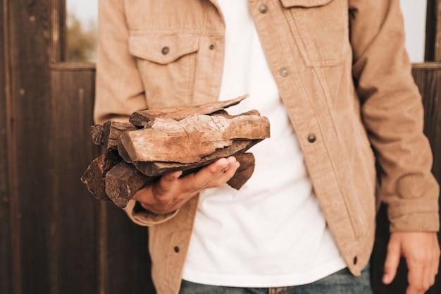 Vooraanzicht man carring brandhout