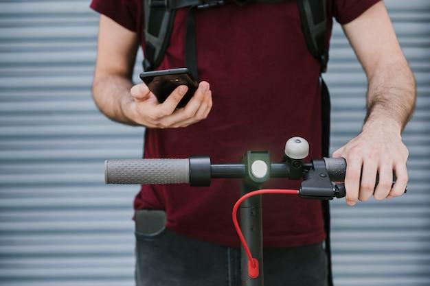 Vooraanzicht man die telefoon op e-scooter