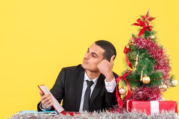 Vooraanzicht man in pak zittend aan de tafel kijken naar rechts duim omhoog teken kerstboom en geschenken