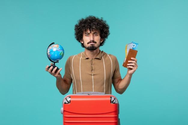 Vooraanzicht man in vakantie met globe en ticket op blauw
