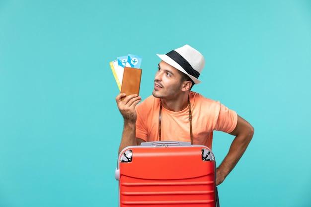 Vooraanzicht man in vakantie met zijn kaartjes op blauw